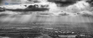 Aerial photo looking toward Manchester City Centre with sun rays beaming down between clouds